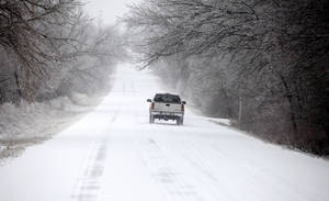 photo - A motorist drives on a snow packed Midwest Blvd. in Edmond, Oklahoma January 29, 2010. Photo by Steve Gooch, The Oklahoman