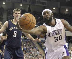 Photo - Sacramento Kings forward Reggie Evans, right, reaches for a rebound against New Orleans Pelicans center Jeff Withey (5) during the third quarter of an NBA basketball game in Sacramento, Calif., Monday, March 3, 2014.  The Kings won 96-89.(AP Photo/Rich Pedroncelli)