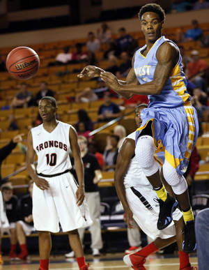 Photo - Putnam City West's Omega Harris (5) passes the ball near Mustang's Terrell Williams (10) during a Class 6A boys semifinal high school basketball game in the state championship tournament between Putnam City West and Mustang at the Mabee Center in Tulsa, Okla., Friday, March 14, 2014. Photo by Nate Billings, The Oklahoman