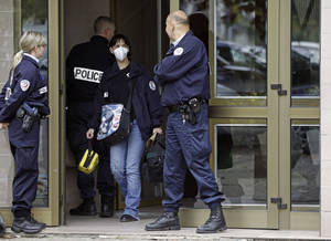 photo -   French police officers stand guard at the entrance of a building in Strasbourg, France, Saturday Oct. 6, 2012, where a suspect was shot dead after firing at police. French anti-terrorism forces carried out raids in cities nationwide on Saturday, at least five people were arrested in the investigation into the firebombing of a kosher grocery outside Paris last month. (AP Photo/Jean Francois Badias)