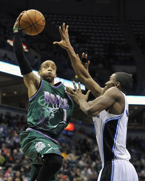 photo - Milwaukee Bucks' Monta Ellis, left, drives to the basket over Orlando Magic's Moe Harkless during the second half of an NBA basketball game on Saturday, Feb. 2, 2013, in Milwaukee. (AP Photo/Jim Prisching)