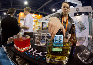 Photo - HZO representative Devin Markle pulls a smart phone out of a container of beer after demonstrating the company's WaterBlock technology at the Consumer Electronics Show, Wednesday, Jan. 9, 2013, in Las Vegas. WaterBlock is a nanobacking that coats the inner circuits of a device. (AP Photo/Julie Jacobson)