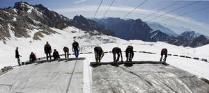 Photo - FILE - In this May 10, 2011 file photo, workers cover the glacier with oversized plastic sheets on the peak of Germany's highest mountain Zugspitze (2962 meters) near Garmisch-Partenkirchen, southern Germany. The sheets are meant to keep the glacier from melting during the summer months. It's Plan B in the fight against climate change: cooling the planet by sucking heat-trapping CO2 from the air or reflecting sunlight back into space. The U.N.'s expert panel on climate change is under pressure from both sides this week in Berlin, Germany, as it considers whether geoengineering should be part of the toolkit that governments use to keep global warming in check. (AP Photo/Matthias Schrader, File)