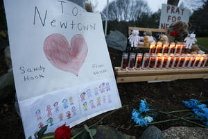Photo - A child's message rests with a memorial for shooting victims, Sunday, Dec. 16, 2012, in Newtown, Conn. A gunman walked into Sandy Hook Elementary School in Newtown on Friday and opened fire, killing 26 people, including 20 children. (AP Photo/Jason DeCrow)