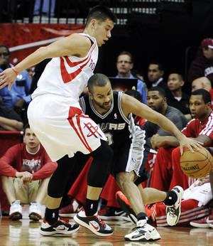Photo - San Antonio Spurs' Tony Parker, right, pushes against Houston Rockets' Jeremy Lin in the first half of an NBA basketball game, Monday, Dec. 10, 2012, in Houston. (AP Photo/Pat Sullivan)