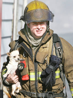 photo - Oklahoma City firefighter C.J. Seitz carries a dog from a house fire in the 2400 block of NW 2 in Oklahoma City on Monday. Photo BY STEVE GOOCH, THE OKLAHOMAN