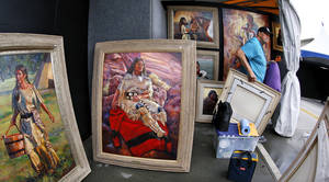 Photo -  Guadalupe Apodaca hangs his oil paintings as he arranges his artwork inside his booth for this year's Festival of the Arts in downtown Oklahoma City on Monday. Apodaca is from Scottsdale, Ariz., and said he has been showing his work off and on at the Oklahoma City festival since the early 1970s, before it moved to its current location on S. Hudson. Apodaca surmised this is probably his 15th time to have a booth at the Festival of the Arts. Photo by Jim Beckel, The Oklahoman  <strong>Jim Beckel -   </strong>