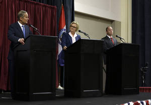 Photo -   Republican Rep. Todd Akin, left, speaks as Democratic Sen. Claire McCaskill, center, and Libertarian Jonathan Dine listen during the first debate in the Missouri Senate race Friday, Sept. 21, 2012, in Columbia, Mo. (AP Photo/Jeff Roberson)