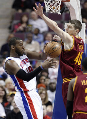 Photo - Detroit Pistons center Greg Monroe (10) passes the ball against Cleveland Cavaliers center Tyler Zeller (40) in the first half of an NBA basketball game Friday, Feb. 1, 2013, in Auburn Hills, Mich. (AP Photo/Duane Burleson)