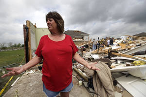 photo -   Sherry Enochs, stands in what is left of her home as she recounts the tornado that struck her home Wednesday, April 4, 2012, in Forney, Texas. Enochs was babysitting three children all under the age of 3, when the tornado struck. All survived the storm with minor bumps and bruises. (AP Photo/Tony Gutierrez)