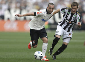 Photo - Corinthians's Guilherme, left, fights for a ball with  Figueirense's Guilherme Lazaroni during a Brazilian soccer league match at the Itaquerao, the still unfinished stadium, in Sao Paulo, Brazil, Sunday, May 18, 2014. Only 40,000 tickets were put on sale for Corinthians' match against Figueirense because some of the 20,000 temporary seats needed for the World Cup opener are still being installed. The stadium will host the World Cup opener match between Brazil and Croatia on June 12. (AP Photo/Andre Penner)