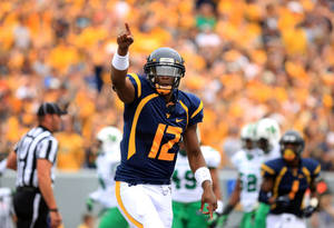Photo -   West Virginia University quaterback Geno Smith celebrates his touchdown pass against Marshall during an NCAA college footbal game in Morgantown, W.Va., Saturday, Sept. 1, 2012. (AP Photo/Christopher Jackson)