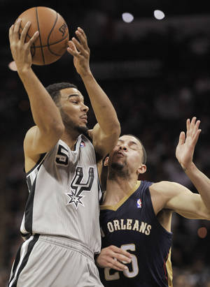Photo - San Antonio Spurs guard Cory Joseph, left, collides with New Orleans Pelicans guard Austin Rivers during the first half of an NBA basketball game on Saturday, March 29, 2014, in San Antonio. (AP Photo/Darren Abate)