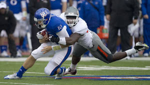 Photo -   Kansas quarterback Dayne Crist (10) is tackled by Oklahoma State defensive tackle Nigel Nicholas (89) during the first half of an NCAA college football game in Lawrence, Kan., Saturday, Oct. 13, 2012. (AP Photo/Orlin Wagner)