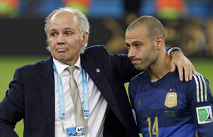 Photo - Argentina's head coach Alejandro Sabella stands with Javier Mascherano (14) after the World Cup final soccer match between Germany and Argentina at the Maracana Stadium in Rio de Janeiro, Brazil, Sunday, July 13, 2014. Germany won the match 1-0. (AP Photo/Matthias Schrader)
