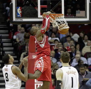 Photo - Houston Rockets center Dwight Howard, center, dunks over Phoenix Suns' Channing Fry, left, and Goran Dragic in the first half of an NBA basketball game on Wednesday, Feb. 5, 2014, in Houston. (AP Photo/Bob Levey)