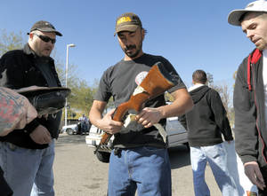 Photo - Gun buyers inspect their purchases outside a police station in Tucson, Ariz. on Tuesday, Jan 8, 2013. About a dozen buyers offered cash to sellers in the parking lot of a police station where Tucson City Councilman Steve Kozachik set up a gun buyback program in exchange for a $50 gift certificate to a grocery store. The buyers were trying to purchase weapons from sellers in an effort to circumvent Councilman Kozachik's buyback program. (AP Photo/Matt York)