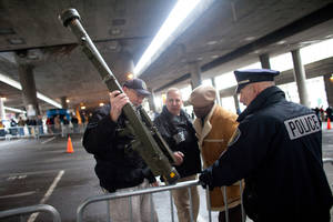 photo - RETRANSMISSION TO CORRECT WEAPON TYPE - Seattle Police Department officers examine an inert surface to air missile launcher brought to the gun buy back program run by the Seattle Police Department on Saturday, January 26, 2013. The city has collected donations totaling nearly $120,000 to pay for a series of gun buyback events. Participants have been asked to unload and secure their weapons in the trunk of their vehicle or in a locked container. (AP Photo/seattlepi.com, Joshua Trujillo) MAGS OUT; NO SALES; SEATTLE TIMES OUT; MANDATORY CREDIT; TV OUT