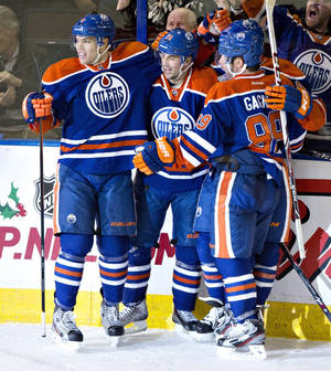 Photo - Edmonton Oilers' Taylor Hall (4), Jordan Eberle (14) and Sam Gagner (89) celebrate the game winning goal against Carolina Hurricanes during overtime NHL hockey action in Edmonton, Alberta, on Tuesday, Dec. 10, 2013. (AP Photo/The Canadian Press, Jason Franson)