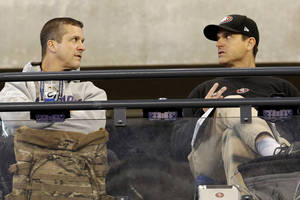 Photo - San Francisco 49ers head coach Jim Harbaugh, right, talks with Baltimore Ravens head coach John Harbaugh at the NFL football scouting combine in Indianapolis, Saturday, Feb. 22, 2014. (AP Photo/Nam Y. Huh)