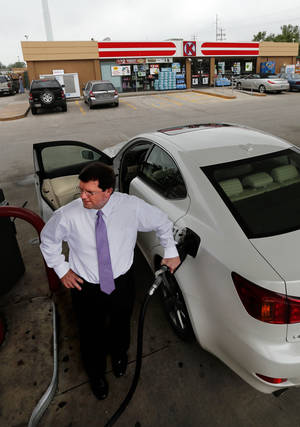 Photo - Brian Young buys gasoline Friday in Norman as Oklahoma consumers and station owners feel the crunch of high gas prices. Photo by Steve Sisney, The Oklahoman <strong>STEVE SISNEY - THE OKLAHOMAN</strong>