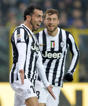 Photo - Juventus' Carlos Tevez celebrates after scoring as teammate Claudio Marchisio, right, watches him, during a Serie A soccer match between Juventus and Atalanta, in Bergamo, Italy, Sunday, Dec. 22, 2013. (AP Photo/Daniele Badolato, Lapresse)