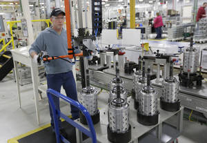 photo - FILE - In this Thursday, Feb. 28, 2013 file photo, Dietz Werland works on the assembly line during a media tour before an investment and jobs announcement event at the Chrysler transmission plat in Kokomo, Ind. (AP Photo/AJ Mast, File)
