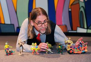 Photo - Kevin Stark poses with toys on display at the Toy and Action Figure Museum in Pauls Valley, Photo by Calli Henry