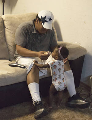 Photo - Greg Rogers, shown here with his daughter Triumph, said he worries about his family's lack of health coverage, but he can't afford it while paying $27,000 over three years for apprenticeship certification. Photo by Heather Brown for The Oklahoman  <strong></strong>