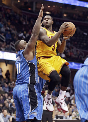 Photo - Cleveland Cavaliers' Dion Waiters, right, jumps to the basket against Orlando Magic's Glen Davis during the second quarter of an NBA basketball game Thursday, Jan. 2, 2014, in Cleveland. (AP Photo/Tony Dejak)