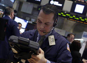 Photo - Trader Michael Zicchinolfi works on the floor of the New York Stock Exchange, Thursday, Dec. 19, 2013. Stocks edged lower in early trading Thursday, pulling back from record levels. (AP Photo/Richard Drew)