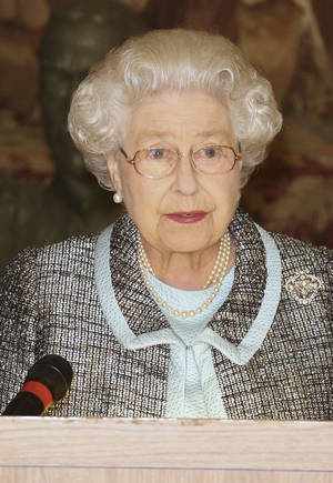 photo - Britain's Queen Elizabeth II, Head of the Commonwealth signs the Commonwealth Charter at a reception at Marlborough House, London  Monday March 11, 2013. The Charter is an historic document which brings together, for the first time in the associations 64-year history, key declarations on Commonwealth principles. (AP Photo/ Philip Toscano/PA) UNITED KINGDOM OUT