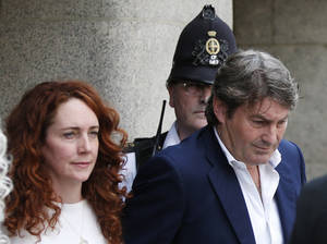 Photo - Rebekah Brooks, former News International chief executive, left, accompanied by her husband Charlie Brooks, leaves the Central Criminal Court in London, Tuesday, June 24, 2014. Former News of the World editor Andy Coulson was convicted of phone hacking Tuesday, but fellow editor Rebekah Brooks was acquitted after a months-long trial centering on illegal activity at the heart of Rupert Murdoch's newspaper empire. A jury at London's Old Bailey unanimously found Coulson, the former spin doctor of British Prime Minister David Cameron, guilty of conspiring to intercept communications. Brooks was acquitted of that charge and of counts of bribing officials and obstructing police. The nearly eight-month trial was triggered by revelations that for years the News of the World used illegal eavesdropping to get stories, listening in on the voicemails of celebrities, politicians and even crime victims. (AP Photo/Lefteris Pitarakis)