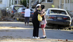 Photo -   People embrace on a street damaged yesterday's tornado in Springfield, Mass., Thursday, June 2, 2011. Residents of 19 small communities in central and western Massachusetts were left to deal with widespread damage Thursday, one day after at least two late-afternoon tornadoes shocked emergency officials and residents more accustomed to dealing with snow and bone-chilling cold than funnel clouds spawned by spring storms. (AP Photo/Jessica Hill)