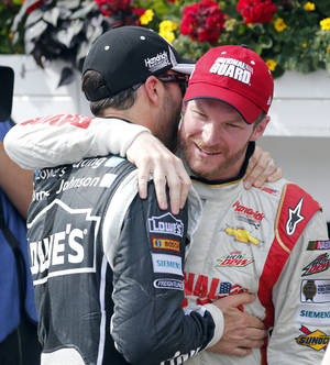 Photo - Jimmie Johnson, left, congratulates Dale Earnhardt Jr. after Earnhardt won the NASCAR Sprint Cup Series Pocono 400 auto race at Pocono Raceway on Sunday, June 8, 2014, in Long Pond, Pa. (AP Photo/Mike Groll)