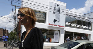 Photo - Passers-by walk down the street past the American Apparel store in the Shadyside neighborhood of Pittsburgh on Wednesday, July 9, 2014. American Apparel Inc. has reached a preliminary deal with investment firm Standard General to receive $25 million in financing to bolster the clothing chain's finances, according to a person close to the negotiations.(AP Photo/Keith Srakocic)
