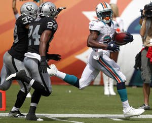 photo -   Miami Dolphins running back Reggie Bush (22) looks back toward Oakland Raiders free safety Michael Huff (24) and strong safety Tyvon Branch (33) while approaching the end zone during the second half of an NFL football game on Sunday, Sept. 16, 2012, in Miami. (AP Photo/Wilfredo Lee)