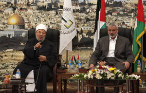 "Photo - Influential Muslim cleric Yusuf al-Qaradawi, left, talks as Gaza's Hamas Prime Minister Ismail Haniyeh listens, during their meeting in Gaza City, Thursday, May 9, 2013. al-Qaradawi has declared that Israel has no right to exist on Thursday and said that ""this land has never once been a Jewish land. Palestine is for the Arab Islamic nation."" The Qatar-based cleric hosts a popular TV show and is widely respected in the Muslim world. (AP Photo/Adel Hana)"