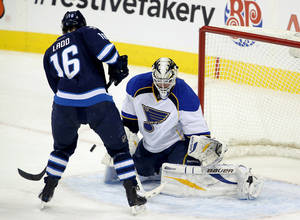Photo - Winnipeg Jets' Andrew Ladd (16) tries to screen St. Louis Blues' goaltender Brian Elliot during first period NHL hockey action in Winnipeg,  Manitoba, Tuesday, Dec. 10, 2013. (AP Photo/The Canadian Press, Trevor Hagan)