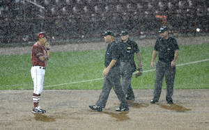 Photo - Oklahoma coach Sunny Golloway talks to the umpires after they suspended play due to rain for a second time in the sixth inning of an NCAA college baseball tournament super regional game against South Carolina in Columbia, S.C., Sunday, June 10, 2012. (AP Photo/Mary Ann Chastain) ORG XMIT: SCMC112