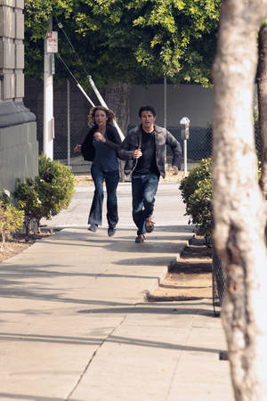 """Photo - Sarah Roemer and Jason Ritter dash down a sidewalk in a scene from """"The Event."""" NBC photos"""