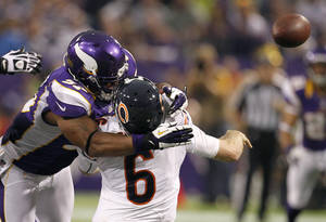 Photo - Chicago Bears quarterback Jay Cutler (6) gets hit by Minnesota Vikings defensive end Everson Griffen, left, after passing the ball during the second half of an NFL football game, Sunday, Dec. 9, 2012, in Minneapolis. Griffen was called for a personal foul on the play. (AP Photo/Genevieve Ross)