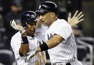 photo -   New York Yankees' Curtis Granderson, left, celebrates with Raul Ibanez after scoring on Ibanez's ninth-inning, two-run home run during their baseball game against the Boston Red Sox at Yankee Stadium in New York, Tuesday, Oct. 2, 2012. The Yankees won 4-3 in the 12th inning. (AP Photo/Kathy Willens)