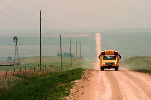 photo - A school bus makes its morning route on a dusty county road in the panhandle of Oklahoma.   Oklahoman Archive photo