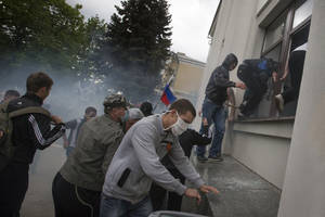 Photo - Pro-Russian activists storm an administration building in the center of Luhansk, Ukraine, one of the largest cities in Ukraine's troubled east, Tuesday, April 29, 2014, as demonstrators demand greater autonomy for Ukraine's regions.  The action on Tuesday further raises tensions in the east, where insurgents have seized control of police stations and other government buildings in at least 10 cities and towns.(AP Photo/Alexander Zemlianichenko)