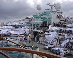 Photo - FILE - This Feb. 10, 2013 file photo provided by Kalin Hill, of Houston, shows passengers with makeshift tents on the the deck of the Carnival Triumph cruise ship at sea in the Gulf of Mexico. About three dozen passengers aboard the ill-fated cruise liner have filed a lawsuit in Miami  hoping to collect thousands of dollars as a result of lingering medical and mental issues they claim were caused by their nightmarish experience. (AP Photo/Kalin Hill, File)