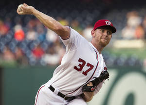 Photo - Washington Nationals starting pitcher Stephen Strasburg delivers a pitch to the Colorado Rockies during the first inning of a baseball game at Nationals Park, on Tuesday, July 1, 2014, in Washington. (AP Photo/ Evan Vucci)