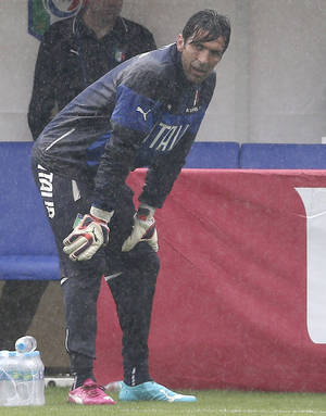 Photo - Italy goalkeeper Gianluigi Buffon stands on the pitch during a rain shower during a training session in Mangaratiba, Brazil, Tuesday, June 10, 2014. Italy will play in group D of the Brazil 2014 soccer World Cup. (AP Photo/Antonio Calanni)