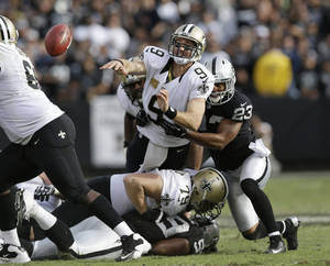 photo -   New Orleans Saints quarterback Drew Brees throws the ball under pressure from Oakland Raiders defensive back Joselio Hanson (23) during the second quarter of an NFL football game in Oakland, Calif., Sunday, Nov. 18, 2012. Players below are New Orleans Saints tackle Bryce Harris (79) and Oakland Raiders defensive end Lamarr Houston (99). (AP Photo/Marcio Jose Sanchez)