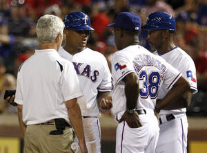 Photo -   Texas Rangers athletic trainer Jamie Reed, left, manager Ron Washington (38) and first base coach Gary Pettis, talk with Adrian Beltre, center rear, after being walked in the third inning of a baseball game against the Cleveland Indians, Wednesday, Sept. 12, 2012, in Arlington, Texas. Beltre left the game following the inning with a shoulder injury. (AP Photo/Tony Gutierrez)